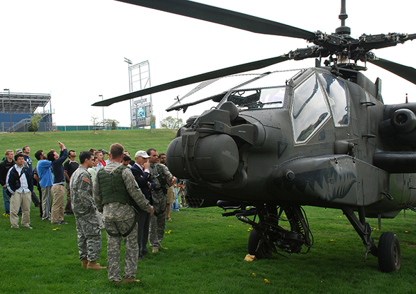 Civilians and military personnel standing outside with an AH64 helicopter.